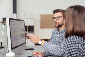 40632548 - proficient young male employee with eyeglasses and checkered shirt, explaining a business analysis displayed on the monitor of a desktop pc to his female colleague, in the interior of a modern office